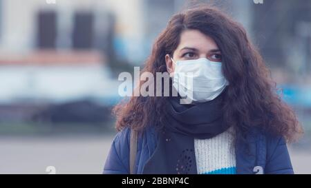 Close-up portrait young europeans woman in protective disposable medical face mask walking outdoors. New coronavirus (COVID-19). Concept of health car Stock Photo