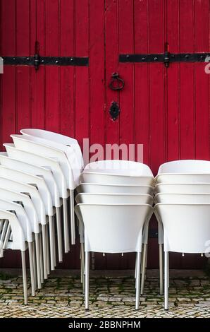 Groups of white chairs stacked together againts a red wooden door - Stock Photo