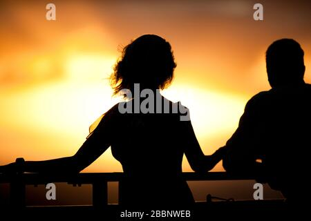 Couple looking at view on cruise ship at sunset. - Stock Photo