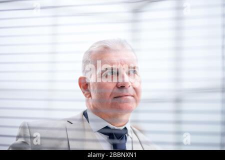 close up. pensive businessman looking through window blinds - Stock Photo