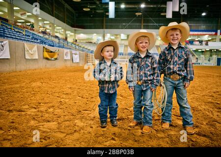 Portrait of three smiling young boys dressed as cowboys at a rodeo arena. - Stock Photo