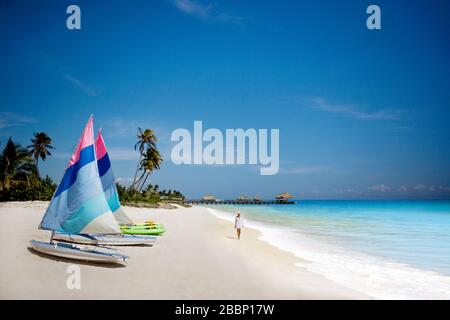 Woman walking along beach next to sailboats - Stock Photo