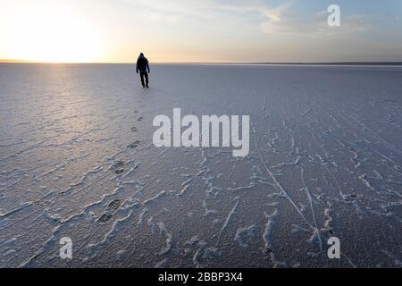 Man walking on salty ground, leaveng foot prints in the dramatic landscape at Tuzbair salt lake, Aktau, Mangystau, Kazakhstan,