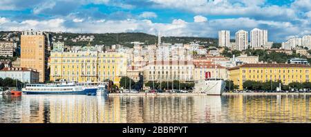 Rijeka - June of 2012, Croatia: Rijeka cityscape reflected in the water, Jadrolinija building and ships in harbor, old and modern buildings - Stock Photo