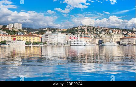 Rijeka - June of 2012, Croatia: View of Rijeka harbor with white ships at the pier, skyline of the city center, sunny day, blue sky with clouds - Stock Photo