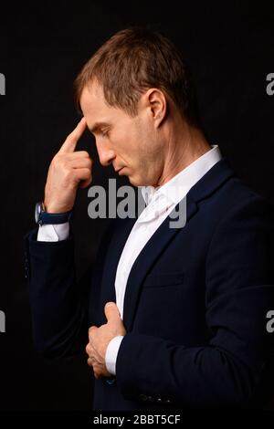 Closeup portrait businessman young man put his finger to his forehead, thinking about the fall of the stock market in New York. Concept of coronavirus - Stock Photo