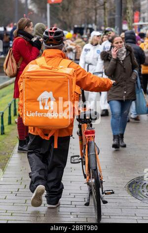 Delivery service Liferando.de, bicycle messenger, pushes the bike on the sidewalk, DŸsseldorf,