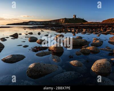 The ruins of Dunstanburgh Castle overlooking the boulder strewn shores of Embleton Bay, Northumberland, England - Stock Photo