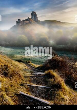 Sunrise on a misty and frosty November morning at Corfe Castle in Dorset, England - Stock Photo