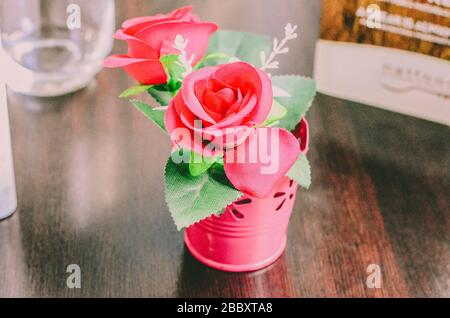 a bouquet of decorative pink roses stands in an iron pail on the table - Stock Photo
