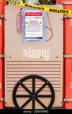 Surrey, Canada - Mar 29, 2020: Children's public playground slide closed due to Coronavirus Covid-19 pandemic - Stock Photo