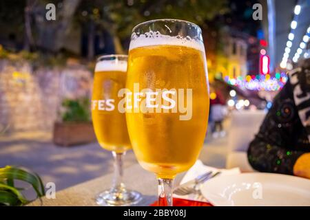 Evening in the Sultanahmet district of Istanbul, Turkey at an outdoor sidewalk cafe with colorful lights and two Turkish Efes beers on the table. - Stock Photo