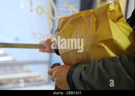 Man pushes the door handle to exit the restaurant after picking up a food order (focus on edge of paper bag) - Stock Photo