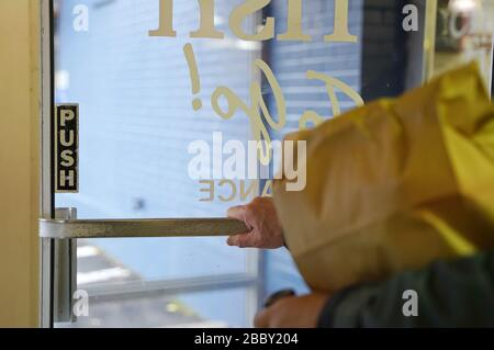 Man pushes the door handle to exit the restaurant after picking up a food order (focus on door) - Stock Photo