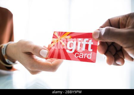 Close-up Of Two Businesspeople Hand Holding Red Gift Card - Stock Photo