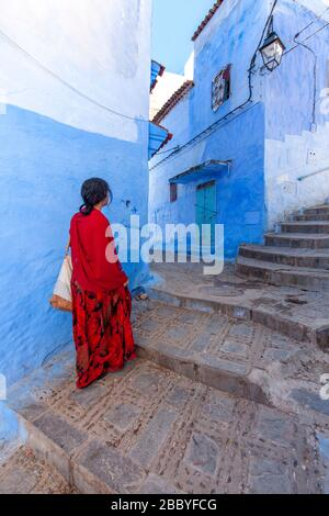Chefchaouen, Morocco: a woman in red walking in the Medina