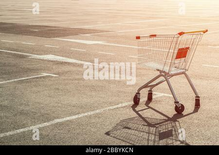 Empty single grocery cart in an empty parking lot near a supermarket at sunset. Panic during a pandemic, goods sold out, out of stock concept. - Stock Photo