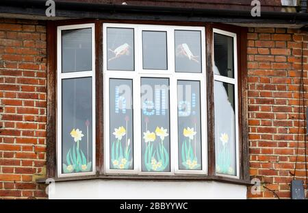 London, UK. 2nd April, 2020 A window in Twickenham decorated with flying angel Barbie Dolls, paper daffodils & a hello sign during the Coronavirus Outbreak Crisis as people stuck in their homes communicate with their neighbourhood. Andrew Fosker / Alamy Live News - Stock Photo