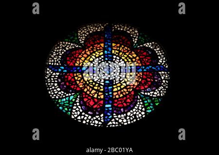 MADABA, JORDAN - FEBRUARY 1, 2020: Amazing stained glass rose mosaic is located over the main entrance of the Moses Memorial Basilica, Mount Nebo, Kingdom of Jordan. Black background - Stock Photo