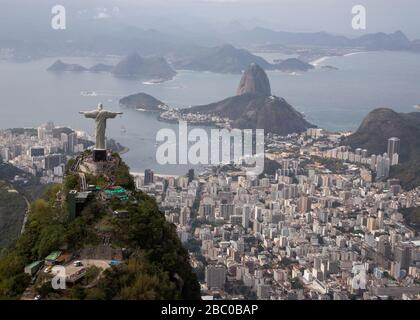 A view of Christ the Redeemer from above with a background of Botafogo bay and the Sugarloaf Mountain in Rio de Janeiro. - Stock Photo