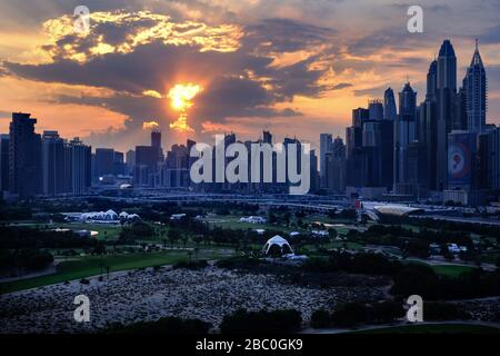 Sunset viewed from 17th floor apartment in Dubai, United Arab Emirates, with golf course in the foreground. - Stock Photo