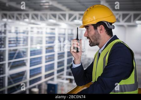 Male supervisor talking, using walkie-talkie on platform in factory - Stock Photo
