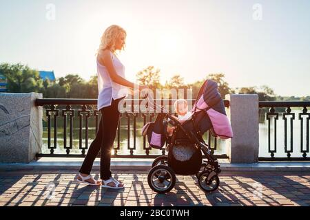 Mothers day. Young mother walking in spring park with infant in baby carriage. Woman spends time with kid outdoors - Stock Photo