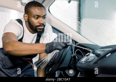 African man, professional car service worker in black protectibe gloves, cleaning car interior with special brushes. Auto detailing and valeting