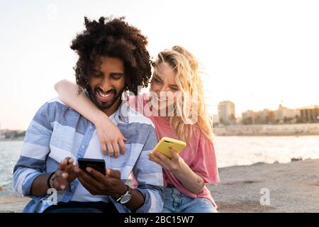 Happy young couple sitting on quay wall at sunset using smartphone - Stock Photo