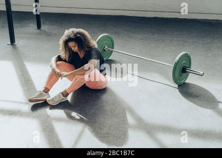 Young woman having a break from exercising in gym - Stock Photo