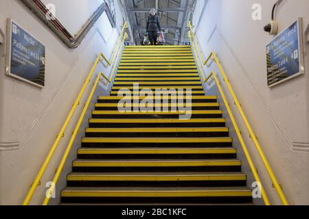 As the second week of the Coronavirus lockdown continues the UK death toll rises by 569 to 2,921, with 1m figure reported cases of Covid-19 being passed worldwide, the empty yellow steps leading up to a platform of Herne Hill rail station in south London, on 2nd April 2020, in London, England. - Stock Photo