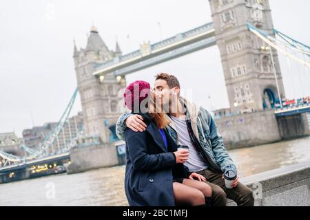 Two young tourists sitting on wall, using smartphone, with  London Bridge in background - Stock Photo