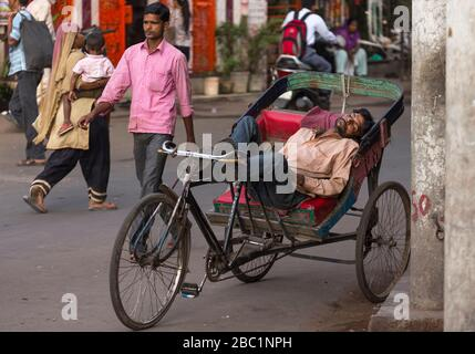 Driver sleeping on his cycle rickshaw in Old Delhi, India - Stock Photo