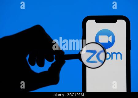 LONDON, UK - April 2nd 2020: Magnifying glass looking at Zoom video conference app on a smartphone - Stock Photo