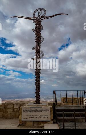 The Brazen Serpent on Mount Nebo, next to Moses Memorial Basilica, Kingdom of Jordan, scenery view with the Promised Lands, Israel. Cloudy winter afternoon sky. - Stock Photo