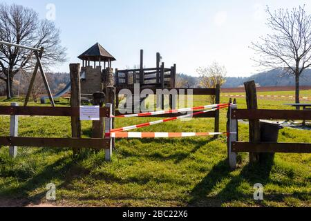 Playground roped off with a sign saying going in is not allowed due to corona virus (COVID19) . Park in Potzbach, Germany on a sunny spring day. - Stock Photo