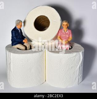 Miniature figurine Pensioners sitting on toilet rolls against a white background - Stock Photo