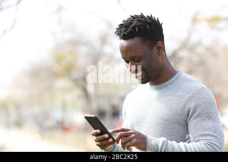 Happy black man using smart phone walking in a park a sunny day - Stock Photo
