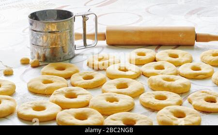 Donut dough is laid out on a table in the kitchen