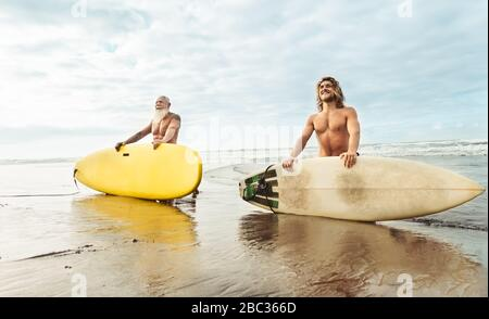 Happy fit friends having fun surfing on tropical ocean - Surfers father and son doing stretching surf exercises