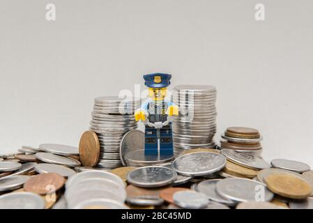 Florianopolis, Brazil, March 28, 2020: Policeman in uniform handcuffed by corruption near coins. Hand cuffed police officer for crime committed. Lego