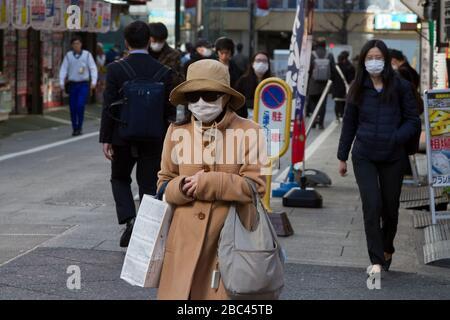 People wearing surgical masks to avoid diseases like the COVID-19 Corona Virus  in Shinjuku, Tokyo, Japan, Thursday February 27th 2020 - Stock Photo