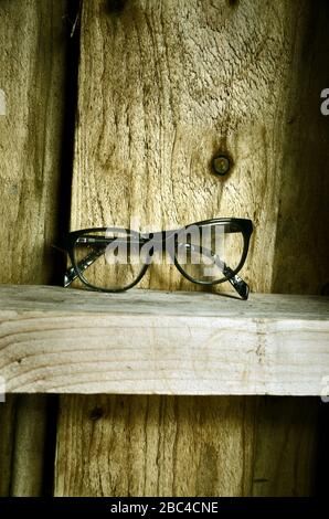A pair of black specs  spectacles sitting on a wooden ledge of a wooden hut. - Stock Photo