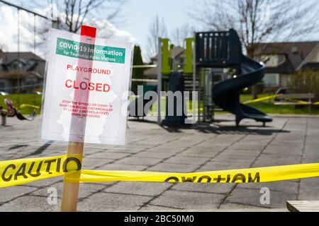 A playground closed sign due to COVID-19 prevention measures infront of a small playground. - Stock Photo