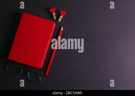 The red notebook stands on a black background, next to the notebook are glasses, a red pencil and two pins in the shape of hearts - Stock Photo