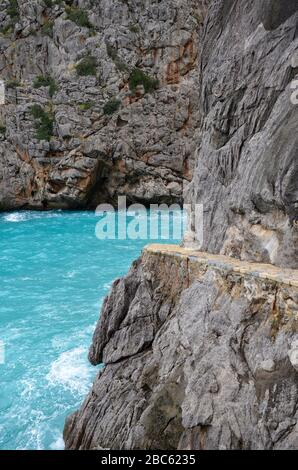 Rocky coast in the North of Balearic island Mallorca, Spain, near the canyon Torrent de Pareis, turquoise mediterranean sea, footpath on the right
