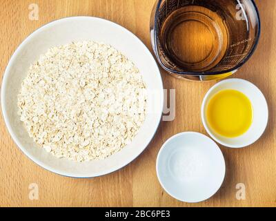 Rolled oats water rapeseed oil and sea salt ingredients for making dairy alternative oat cream on a wooden kitchen table - Stock Photo