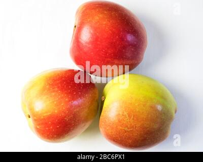Three braeburn apples from above on a white tablecloth - Stock Photo