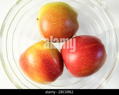 Three braeburn apples in a glass bowl from above on a white tablecloth - Stock Photo