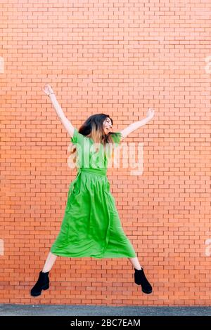 woman in a green dress jumping up and down happily in front of a brick wall. - Stock Photo